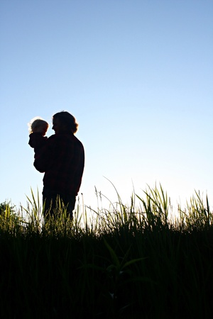 carrying: A silhouette of a father holding his happy toddler son, while standing in grass outside in the evening.