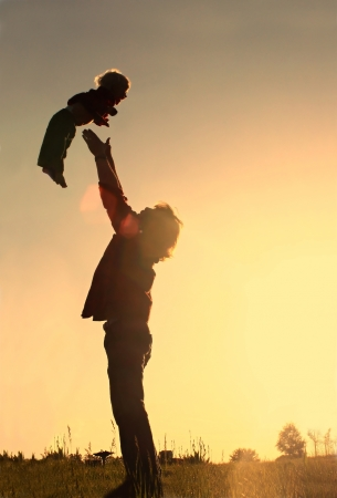 catching: A father throwing his happy, toddler son in the air, silohuetted against a night sky at sunset.