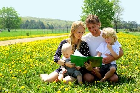 Family Reading Outside in a Field of Dandelions photo