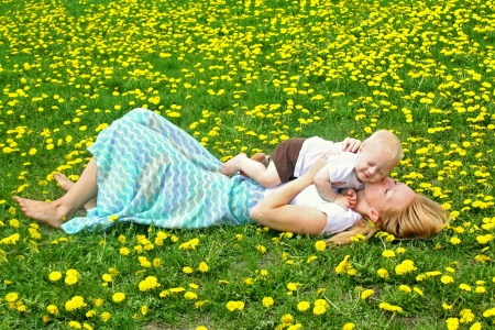 A young, attractive mother, laying in a field of dandelions, kissing her baby boy. photo