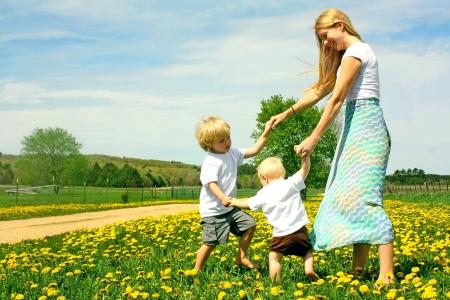 niños bailando: Madre y dos niños de la mano, bailando y jugando fuera