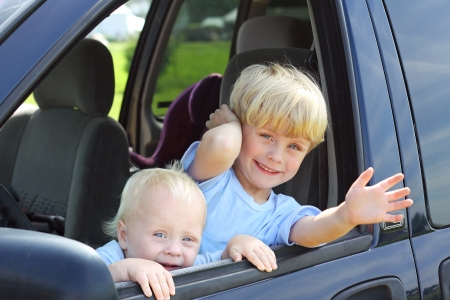 Two cute brothers leaning out a van window, smiling and waving photo