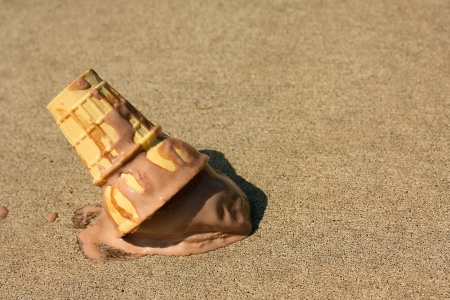 dropped: A melty chocolate ice cream cone has dropped upsidedown onto the sidewalk on a sunny sumer day