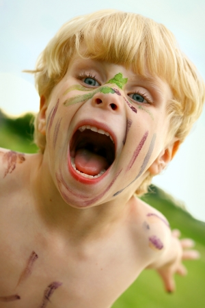 A litle boy growls at the camera with a painted face outside