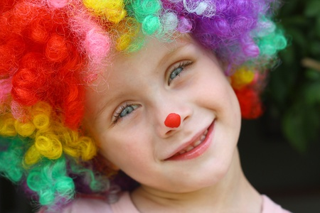 a cute little child dressed up in a clown costume and face paint and smiling