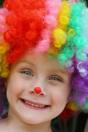 caritas pintadas: un primer plano de un niño sonriente niño lindo vestido con una peluca de payaso disfraces y pintura de la cara Foto de archivo