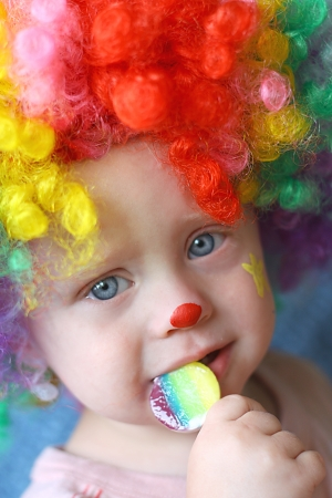 Close up of a cute baby boy dressed up in a clown costume, eating a rainbow sucker photo