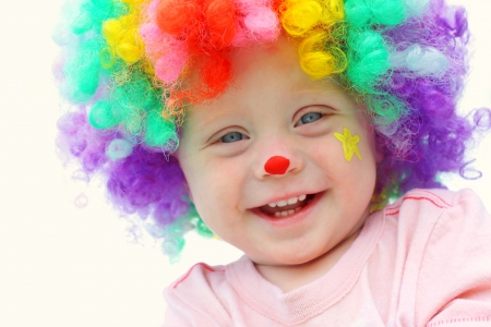 A cute, smiling baby boy is dressed up in a clown wig with clown make up face paint