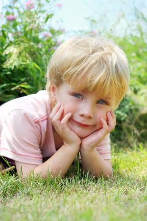 a sweet young child lays in the grass outside by flowers, smiling and resting his head in his hands photo