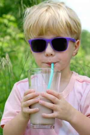 A young child wearing sunglasses is holding a big glass of chocolate milk and sipping it through a straw on a sunny summer day photo