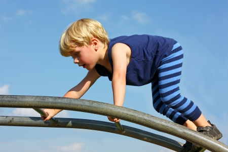 A cute little boy is carefully climbing a ladder toy at the playground on a summer day photo