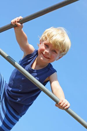 a cute, smiling boy is climbing at a playground on a sunny, summer day photo