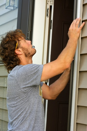 a young, attractive carpenter is installing a storm door on his home photo