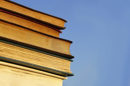 a stack of several old books, novels, and Bibles are piled outside in front of a clear blue sky background photo