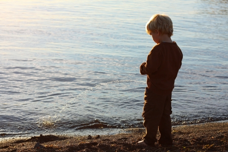 outdoorsman: a young boy child has his back to the camera and is standing on a beach shoreline, peeing into the water.