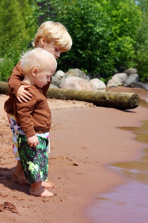 a child is hugging and protecting his baby brother as they stand on the beach near the shore of a lake photo