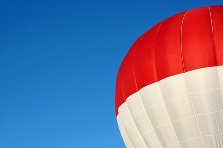 Extreme Close up of a red and white top of an inflated hot air balloon with a blue summer sky background   Sky leaves blank area for copyspace