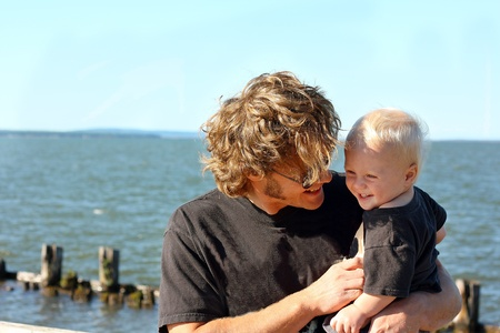 tickling: a close up of a happy, attractive father and his baby son laughing in front of Lake Superior on a sunny summer day. Stock Photo