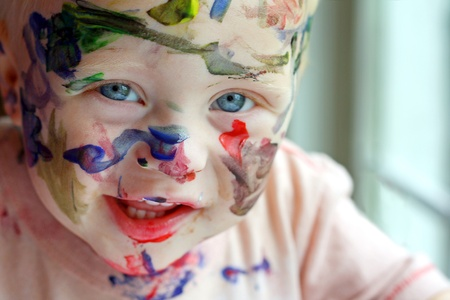 face paint: a close up photo of a baby boy who has covered his entire face in rainbow colored paint