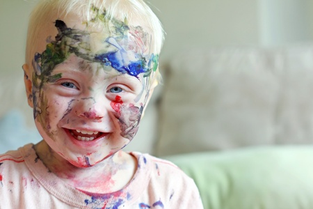 a cute baby boy is laughing after he has covered his entire face in rainbow colored paint Stock Photo