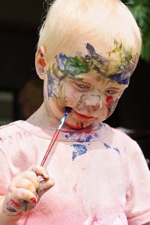 he is different: a cute little baby boy is standing up and looking down as he paints his face all different rainbow colors with a paint brush Stock Photo
