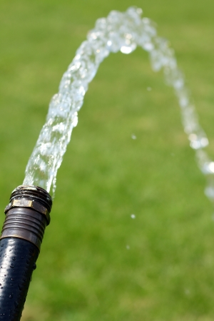 Close Up Of A Black Garden Hose, Spraying Water Onto The Green Grass Of A A