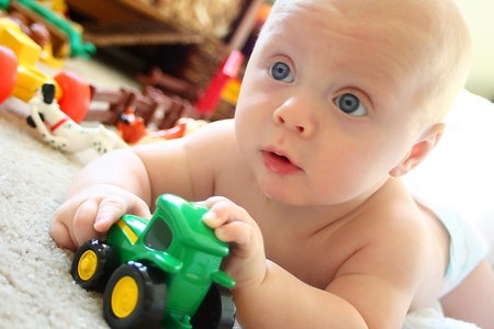 messy room: a cute baby boy with big blue eyes is laying on the floor in his bedroom, playing toy tractors
