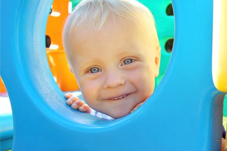a cute baby is smiling with new teeth as he peeks his head through a window hole at a playground on a summer day. photo
