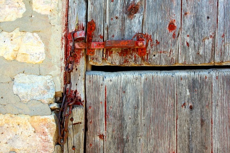 An zoomed in crop of an old wooden barn door with a red latch, next to a stone wall photo