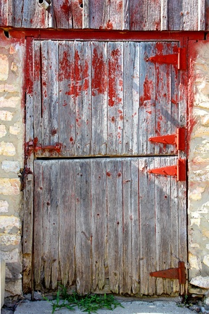 An old wooden barn door with a red latch, next to a stone wall photo