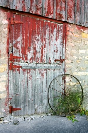 a rustic old barn door with peeling red paint, stone walls, and a rusted antique wagon wheel photo