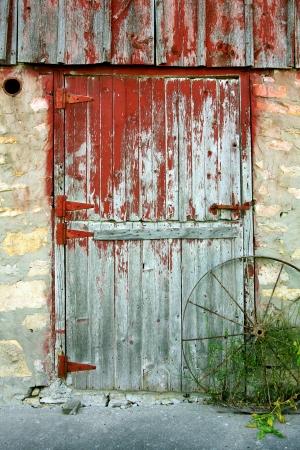 필 링 빨간 페인트, 돌 벽, 그리고 골동품 수레 바퀴와 함께 소박한 오래 된 헛간 문