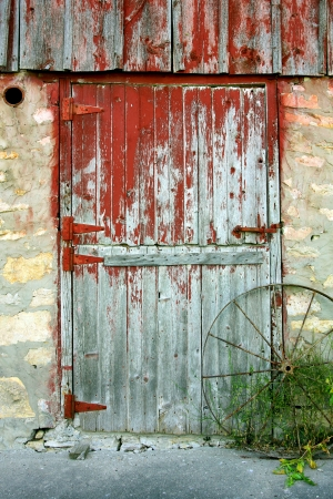 a rustic old barn door with peeling red paint, stone walls, and an antique wagon wheel