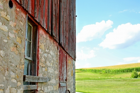 The side of a rustic old barn in front of a blue summer sky and green cornfield photo