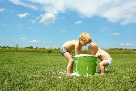 若い子と彼の弟は外で遊んでいる気泡と水のバケツで日当たりの良い夏の日