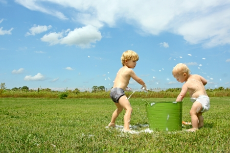 family fight: a young child and his baby brother are playing outside on a summer day with a bucket of soapy water, throwing bubbles at each other