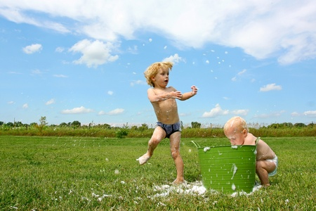 a young child and his baby brother are playing outside on a hot summer day, throwing around bubbles from a bucket of water photo