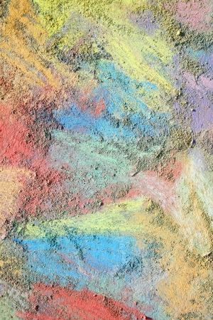 smeared: an abstract background of bright, rainbow colored sidewalk chalk smeared and drawn on the pavement