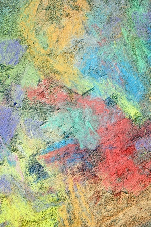 gritty: an abstract background of bright, rainbow colored sidewalk chalk smeared and drawn on the pavement