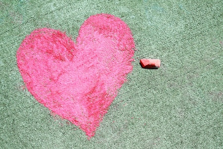 a pink heart symbol is drawn on a sidewalk outside with chalk
