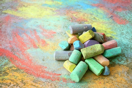 footpath: a collection of colorful sidewalk chalk is piled up on a rainbow drawing, outside on the pavement