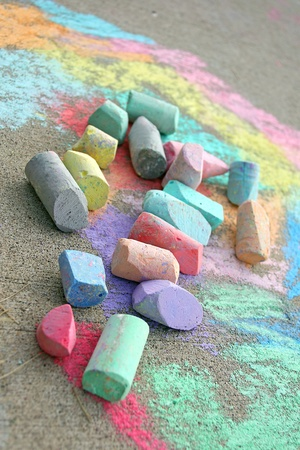 a collection of used, coloful sidewalk chalk is laying on top of a rainbow colored drawing on the pavement