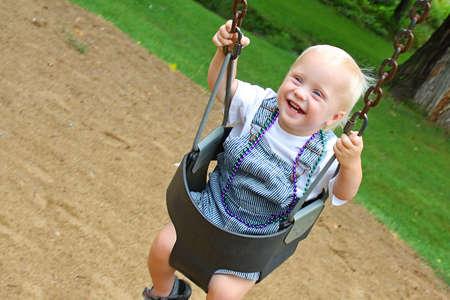 幸せな、笑顔の男の子は日当たりの良い夏の日に公園でスイングします。