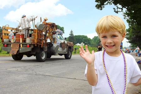 floats: a cute, smiling little boy is waving as he watches floats go by in an American Parade on a summer day Stock Photo