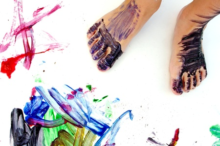 close up on a small child's feet that are covered in paint, standing on a large blank white paper with colorful paintings in the corners.