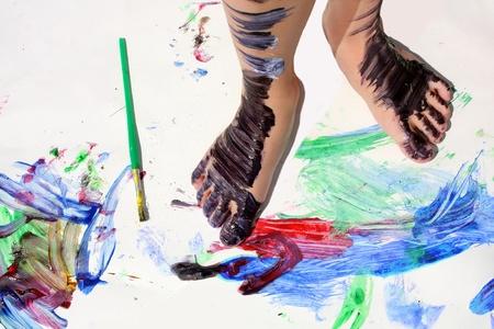 habitacion desordenada: los pies de un niño de corta edad están cubiertas en pintura colorida, ya que están de pie en un pedazo de papel blanco cubierto de pintura de color arco iris. Foto de archivo
