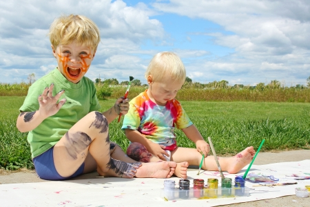 Two happy young children, a little boy and his baby brother, are sitting outside on a summer day, painting a picture, and covering themselves in paint.