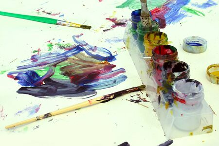 blended: a child has left his paint brushes and colorful paints out on top of a white paper covered in bright artwork.
