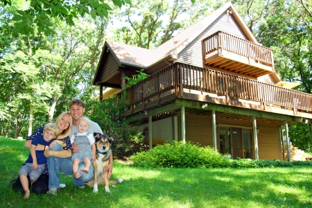 cabaña: un joven atractivo de la familia, feliz de cuatro, la madre, el padre, el bebé y niño pequeño, está sentado afuera con su perro delante de una cabaña preciosa en un día soleado de verano