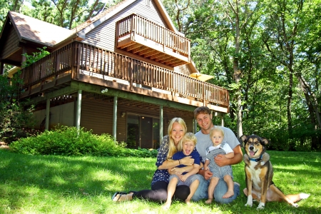 adorable home: a happy, smiling family of four people; mother, father, baby, and young child, and their dog, are sitting in the grass in front of a nice cabin in the woods on a summer day. Stock Photo